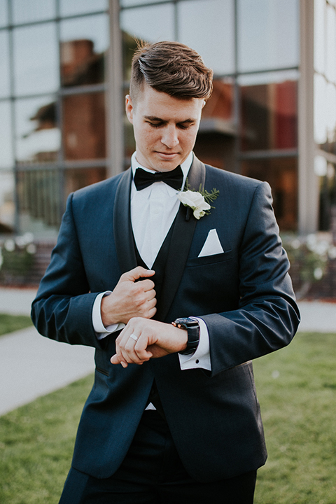 Modern outdoor wedding at long beach museum of art groom navy tuxedo with matching vest and white dress shirt with black bow tie and white pocket square with black watch and white floral boutonniere