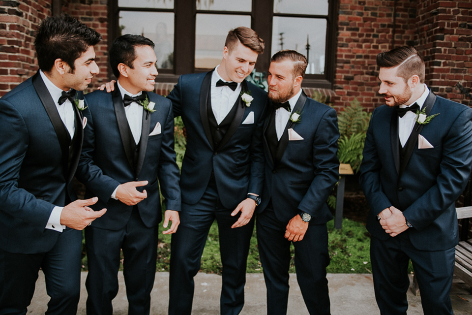 Modern outdoor wedding at long beach museum of art groom and groomsmen navy blue tuxedos with matching vests and white dress shirt with black bow tie and white pocket square with white floral boutonnieres and fun patterned socks