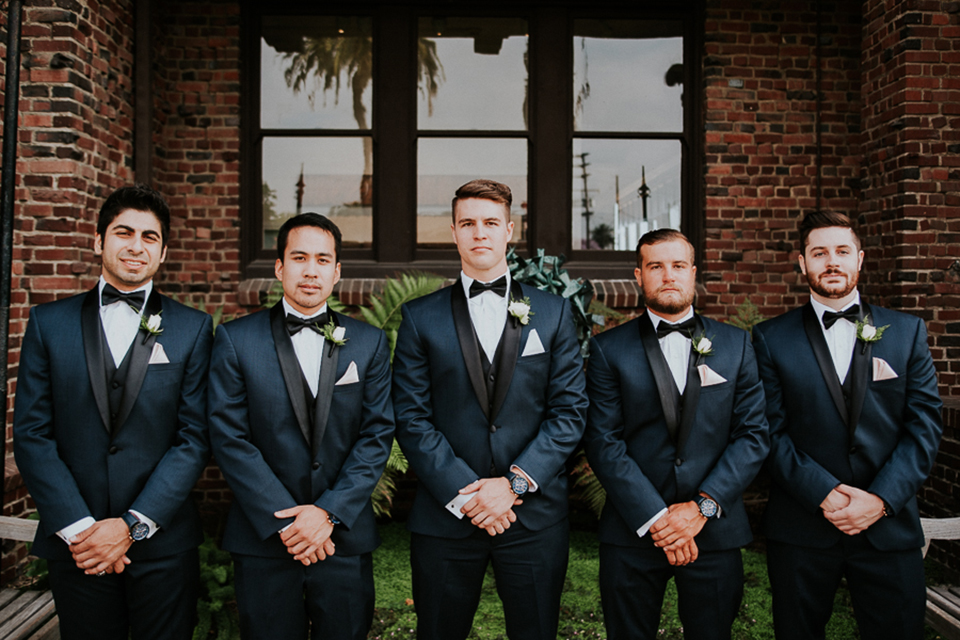 Modern outdoor wedding at long beach museum of art groom and groomsmen navy blue tuxedos with matching vests and white dress shirt with black bow tie and white pocket square with white floral boutonnieres