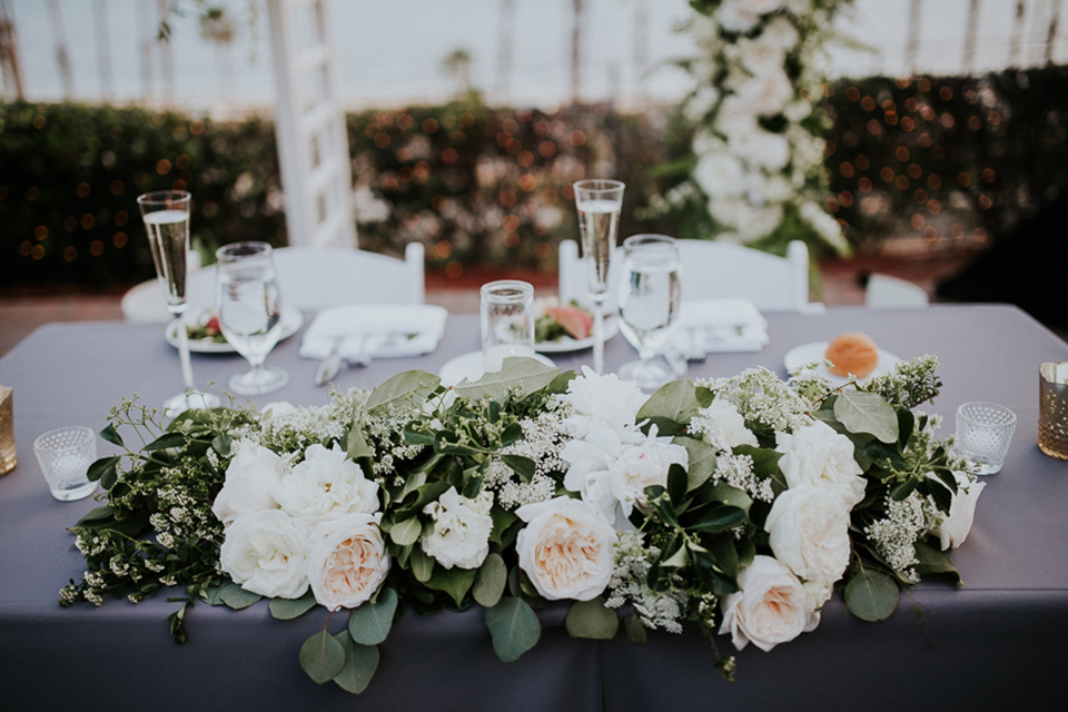 Modern outdoor wedding at long beach museum of art reception area with light grey table linen and white and green flower centerpiece decor with white candles and glass and copper design decor with white chairs and hanging lights