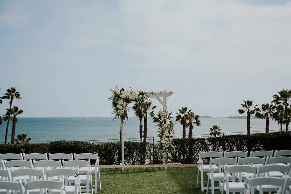 Modern outdoor wedding at long beach museum of art wedding ceremony white chairs on grass and white arch with white and green flower decor overlooking the ocean and palm trees in background wedding photo idea for ceremony