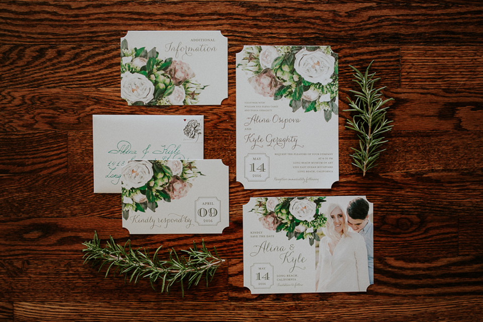 Modern outdoor wedding at long beach museum of art wedding invitations white with light pink and green flower design with picture of bride and groom with greenery flower decor on dark wood background wedding photo idea
