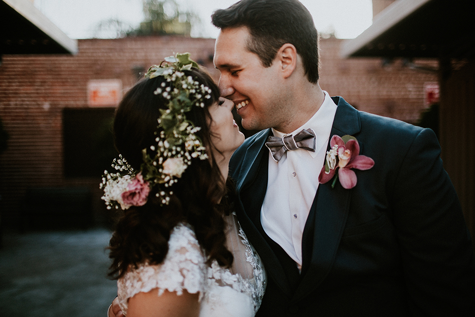 Rustic orange county wedding at the estate on second bride chiffon gown with lace bodice and lace short sleeves and high neckline with white and light pink and green flower crown with groom navy blue suit and white dress shirt with tan bow tie with white trim and pink floral boutonniere smiling