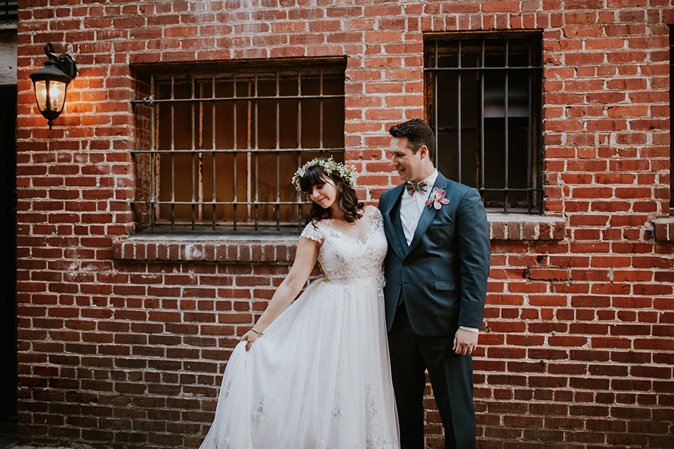 Rustic orange county wedding at the estate on second bride chiffon gown with lace bodice and lace short sleeves and high neckline with white and light pink and green flower crown with groom navy blue suit and white dress shirt with tan bow tie with white trim and pink floral boutonniere hugging