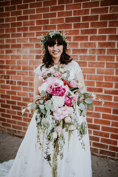 Rustic orange county wedding at the estate on second bride chiffon gown with lace bodice and lace short sleeves and high neckline with white and light pink and green flower crown holding white and pink floral bridal bouquet