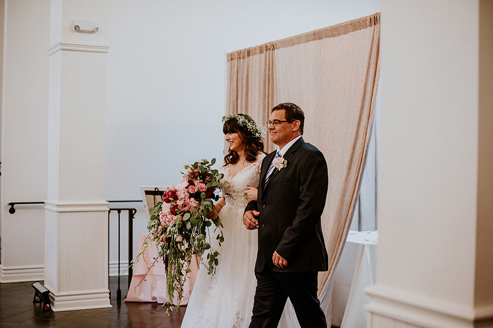 Rustic orange county wedding at the estate on second bride chiffon gown with lace bodice and lace short sleeves and high neckline with white and light pink and green flower crown holding white and pink floral bridal bouquet walking down the aisle with father