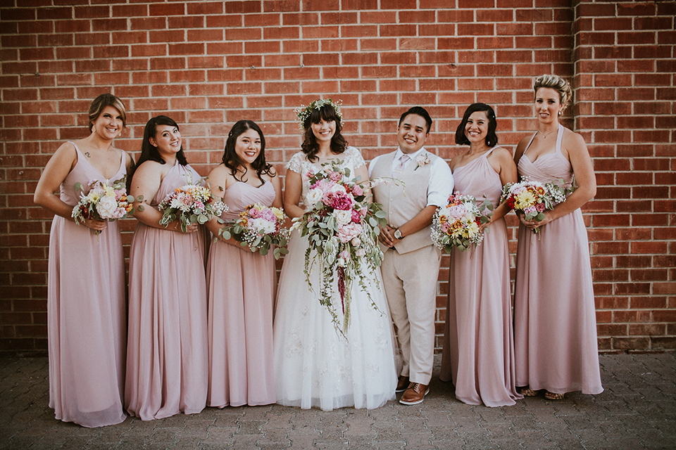 Rustic orange county wedding at the estate on second bride chiffon gown with lace bodice and lace short sleeves and high neckline with white and light pink and green flower crown holding white and pink floral bridal bouquet with bridesmaids long blush pink dresses and guy in tan suit