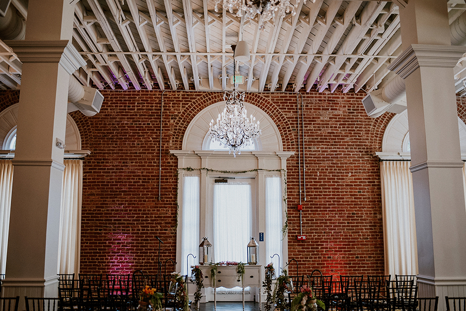 Rustic orange county wedding at the estate on second ceremony set up with dark chairs and white vintage decor with hanging chandelier