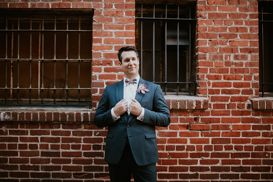 Rustic orange county wedding at the estate on second groom navy blue suit with white dress shirt and tan bow tie with white trim and pink floral boutonniere