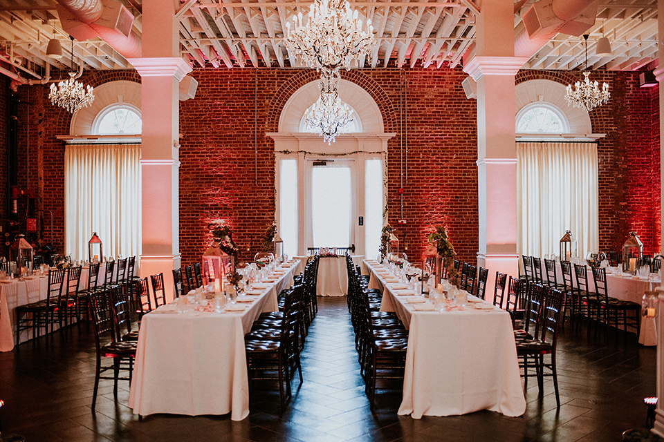 Rustic orange county wedding at the estate on second reception table set up with white table linen and dark chairs with white place settings and pink flower centerpiece decor with candle centerpieces