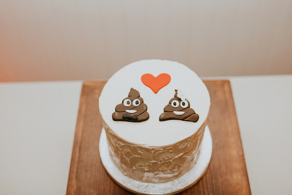 Rustic orange county wedding at the estate on second reception table set up with white table linen and gold table runner with white wedding cake and poop emojis on top with red heart funny wedding cake decoration