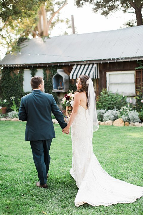 San luis obispo rustic wedding at dana powers house and barn bride strapless mermaid style lace gown with sweetheart neckline and small crystal belt with medium length veil with groom slate blue notch lapel suit with white dress shirt and long navy blue tie with white pocket square and floral boutonniere holding hands