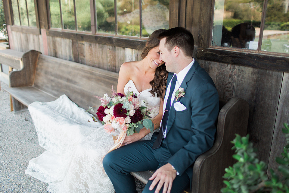 San luis obispo rustic wedding at dana powers house and barn bride strapless mermaid style lace gown with sweetheart neckline and small crystal belt with medium length veil with groom slate blue notch lapel suit with white dress shirt and long navy blue tie with white pocket square and floral boutonniere sitting on bench bride holding floral bridal bouquet