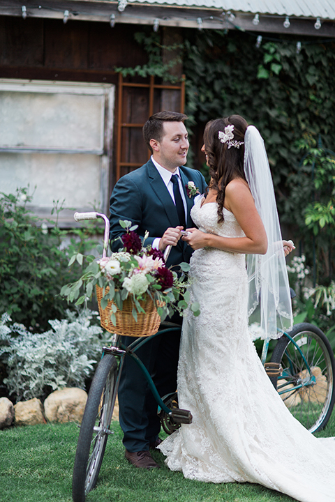San luis obispo rustic wedding at dana powers house and barn bride strapless mermaid style lace gown with sweetheart neckline and small crystal belt with medium length veil with groom slate blue notch lapel suit with white dress shirt and long navy blue tie with white pocket square and floral boutonniere standing by bike with flower decor