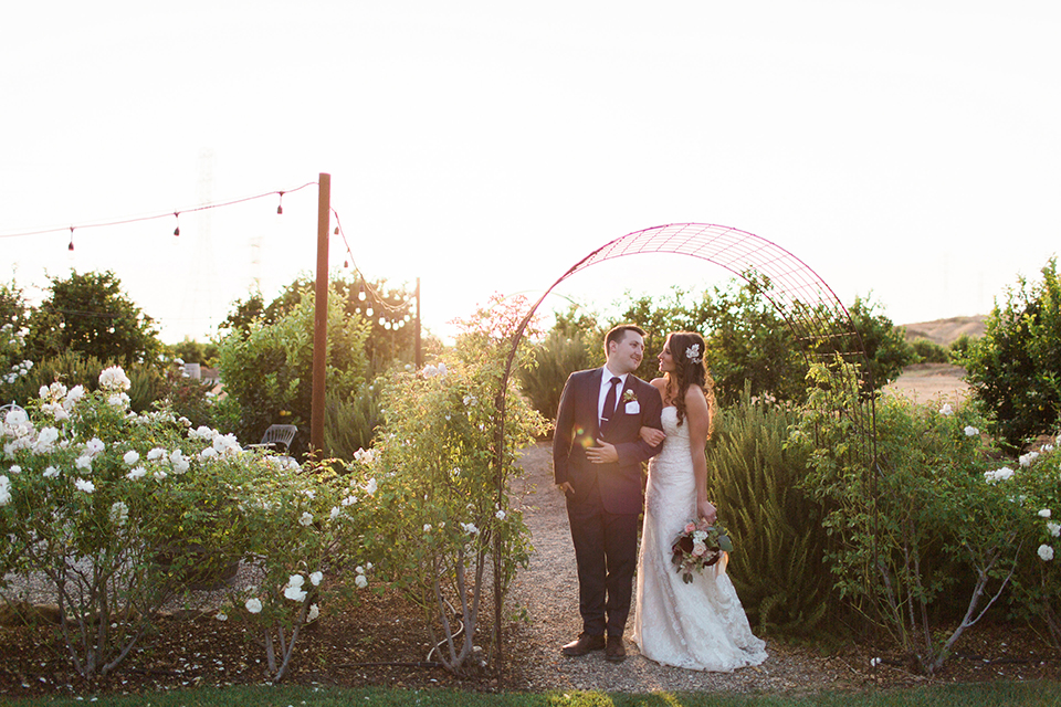 San luis obispo rustic wedding at dana powers house and barn bride strapless mermaid style lace gown with sweetheart neckline and small crystal belt with medium length veil with groom slate blue notch lapel suit with white dress shirt and long navy blue tie with white pocket square and floral boutonniere bride holding floral bridal bouquet sunset