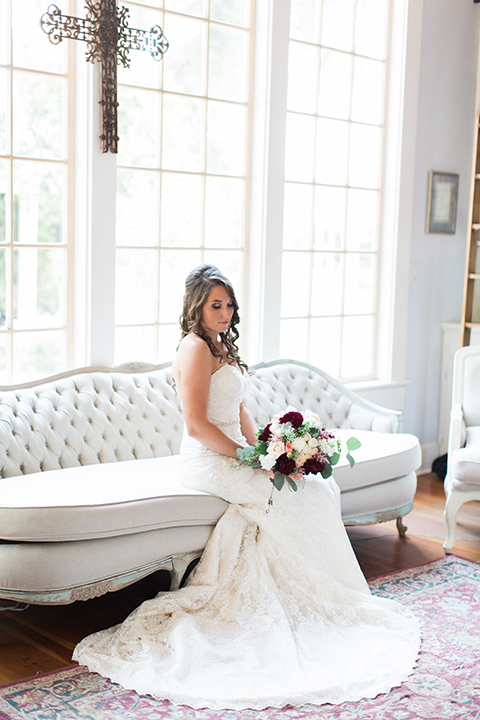 San luis obispo rustic wedding at dana powers house and barn bride strapless mermaid style lace gown with sweetheart neckline and small crystal belt with medium length veil sitting on white couch holding white and dark red floral bridal bouquet