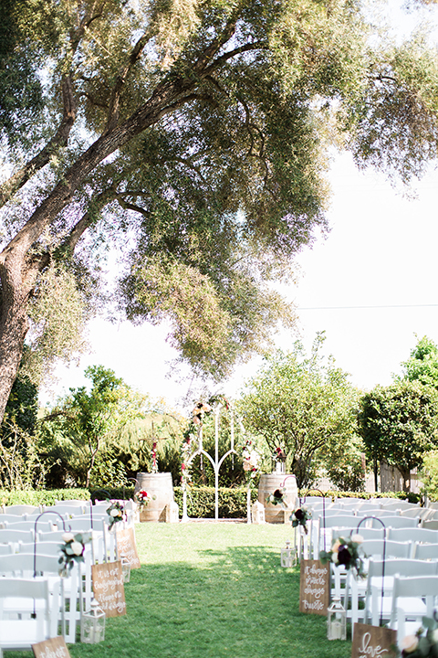 San luis obispo rustic wedding at dana powers house and barn ceremony set up with white chairs and white arch with flower decor and brown wood signs along aisle with flowers on grass wedding photo idea for ceremony