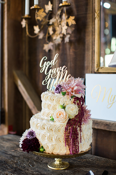San luis obispo rustic wedding at dana powers house and barn reception white two tier wedding cake with flower design and white and dark red flower decor on side with gold cake topper on gold tray on dark brown wood table wedding photo idea