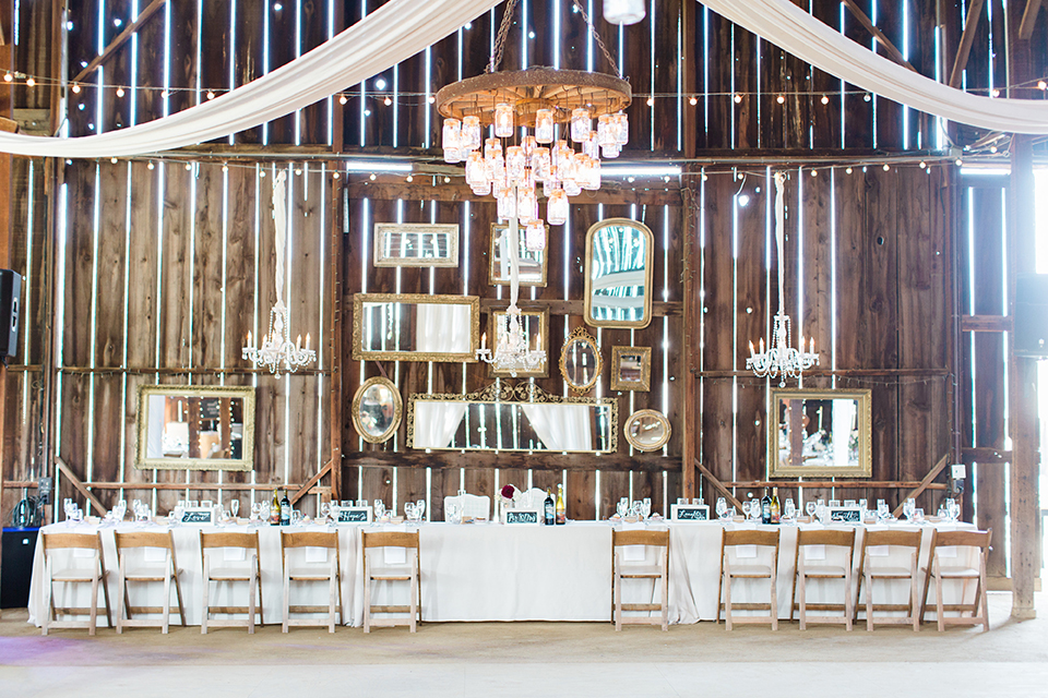 San luis obispo rustic wedding at dana powers house and barn reception white table linen with brown chairs and white chiffon draping on ceiling with hanging light decor and flower and white candle centerpiece decor
