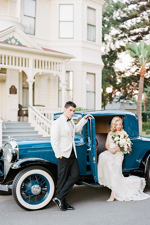 Glamorous outdoor wedding shoot at camarillo ranch house bride form fitting gown with beaded straps and sweetheart neckline with lace designs and groom white dinner jacket with white dress shirt and black pants with black bow tie bride sitting in car holding white floral bridal bouquet