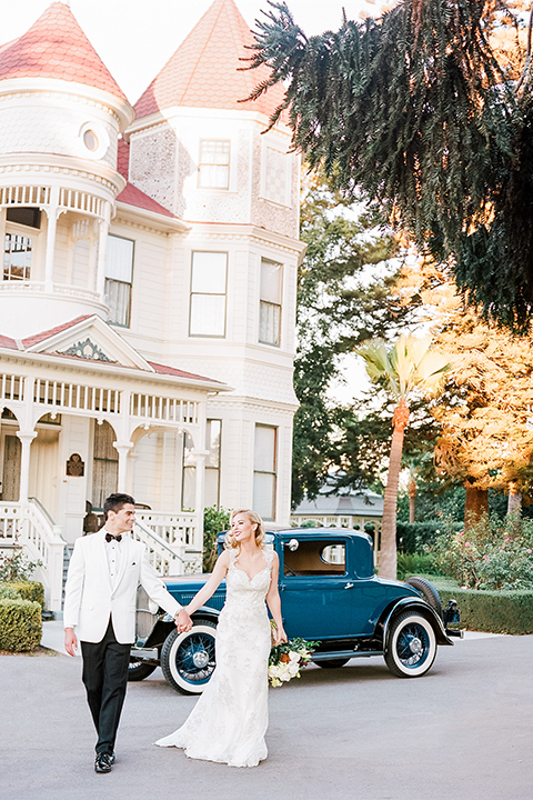 Glamorous outdoor wedding shoot at camarillo ranch house bride form fitting gown with beaded straps and sweetheart neckline with lace designs and groom white dinner jacket with white dress shirt and black pants with black bow tie holding hands