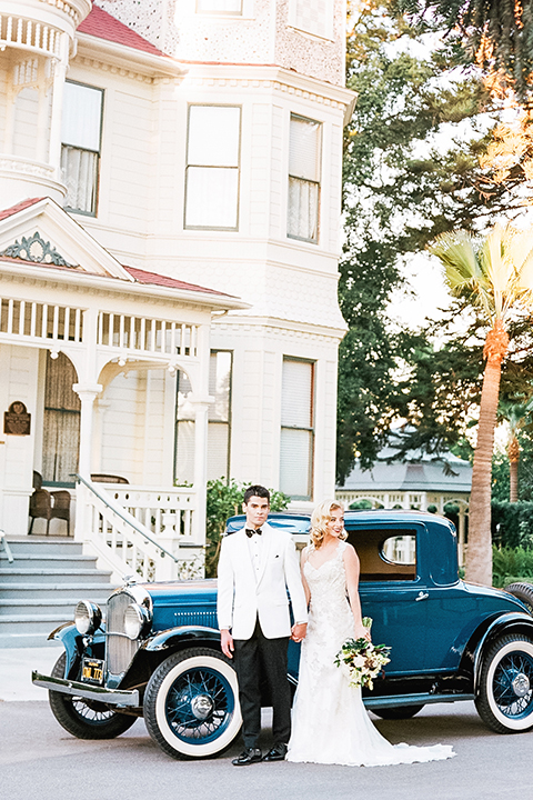 Glamorous outdoor wedding shoot at camarillo ranch house bride form fitting gown with beaded straps and sweetheart neckline with lace designs and groom white dinner jacket with white dress shirt and black pants with black bow tie holding hands by car