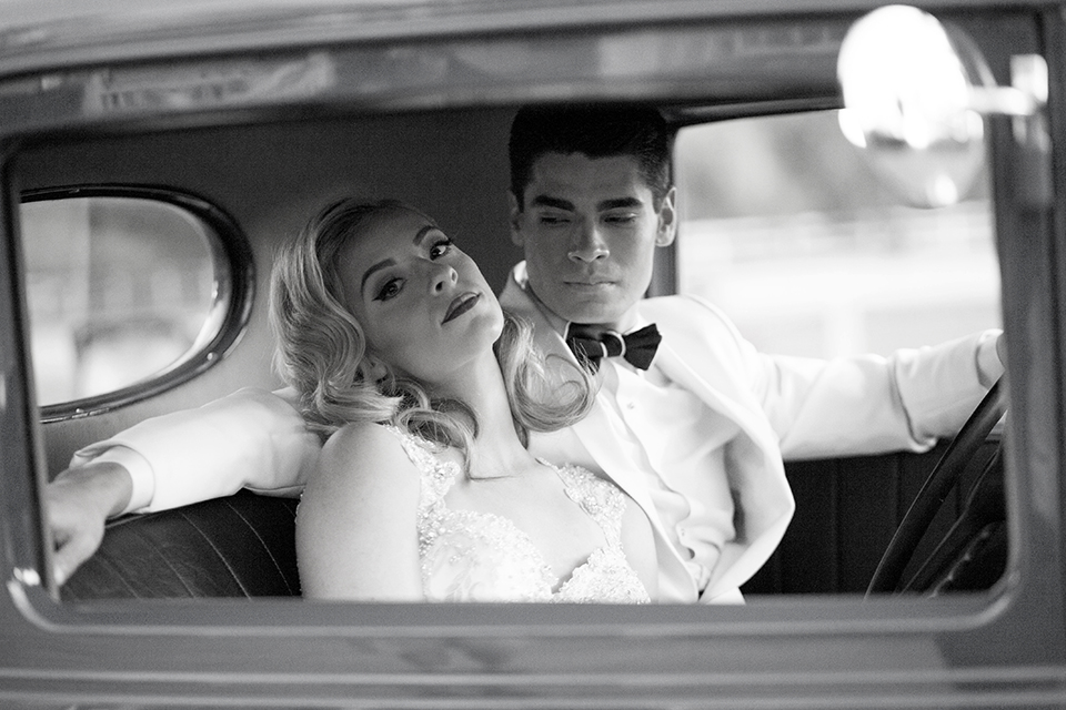 Glamorous outdoor wedding shoot at camarillo ranch house bride form fitting gown with beaded straps and sweetheart neckline with lace designs and groom white dinner jacket with white dress shirt and black pants with black bow tie sitting in car black and white photo