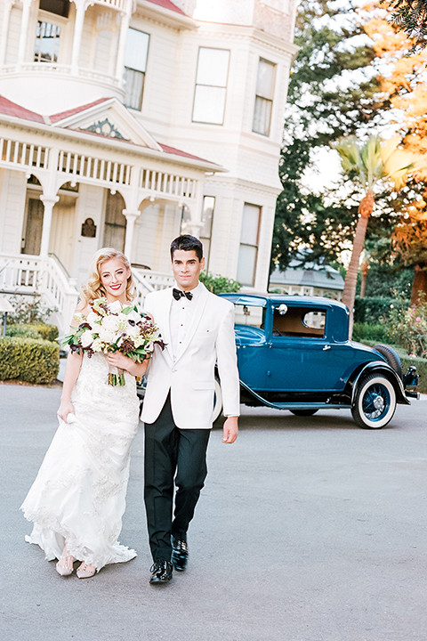 Glamorous outdoor wedding shoot at camarillo ranch house bride form fitting gown with beaded straps and sweetheart neckline with lace designs and groom white dinner jacket with white dress shirt and black pants with black bow tie walking