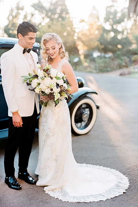 Glamorous outdoor wedding shoot at camarillo ranch house bride form fitting gown with beaded straps and sweetheart neckline with lace designs and groom white dinner jacket with white dress shirt and black pants with black bow tie standing by car bride holding white floral bridal bouquet