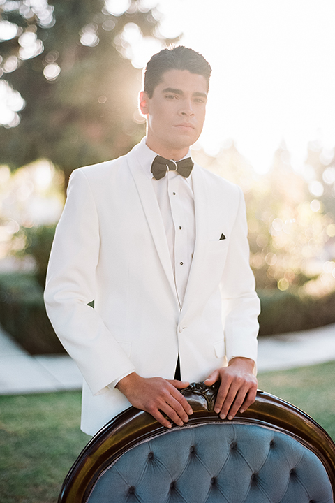 Glamorous outdoor wedding shoot at camarillo ranch house groom white dinner jacket with white dress shirt and black pants with black bow tie standing by chair