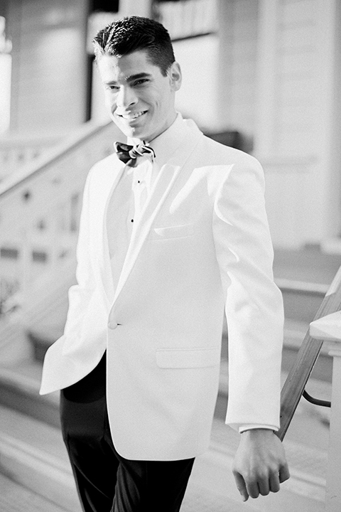 Glamorous outdoor wedding shoot at camarillo ranch house groom white dinner jacket with white dress shirt and black pants with black bow tie black and white photo