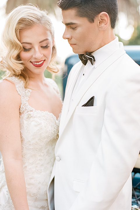 Glamorous outdoor wedding shoot at camarillo ranch house bride form fitting gown with beaded straps and sweetheart neckline with lace designs and groom white dinner jacket with white dress shirt and black pants with black bow tie hugging close up