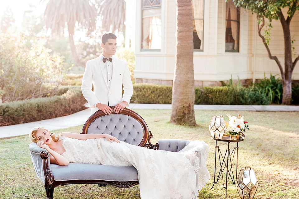 Glamorous outdoor wedding shoot at camarillo ranch house bride form fitting gown with beaded straps and sweetheart neckline with lace designs and groom white dinner jacket with white dress shirt and black pants with black bow tie bride laying on vintage white couch