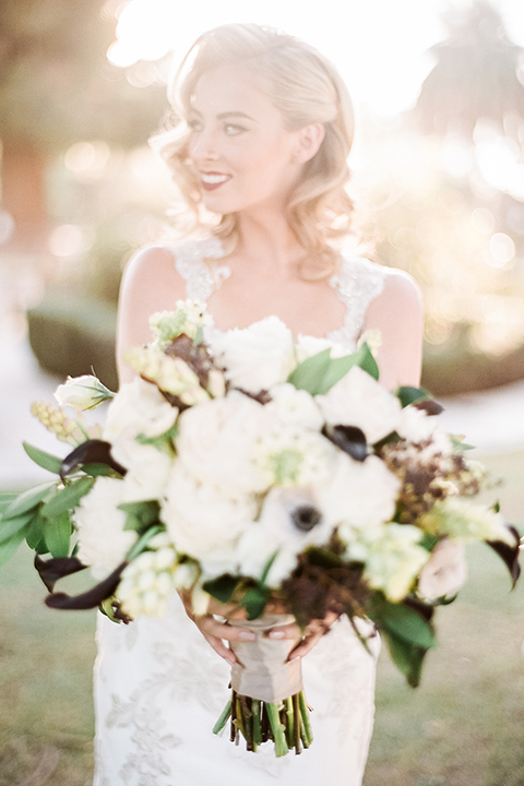 Glamorous outdoor wedding shoot at camarillo ranch house bride form fitting gown with beaded straps and sweetheart neckline with lace designs holding white and green floral bridal bouquet