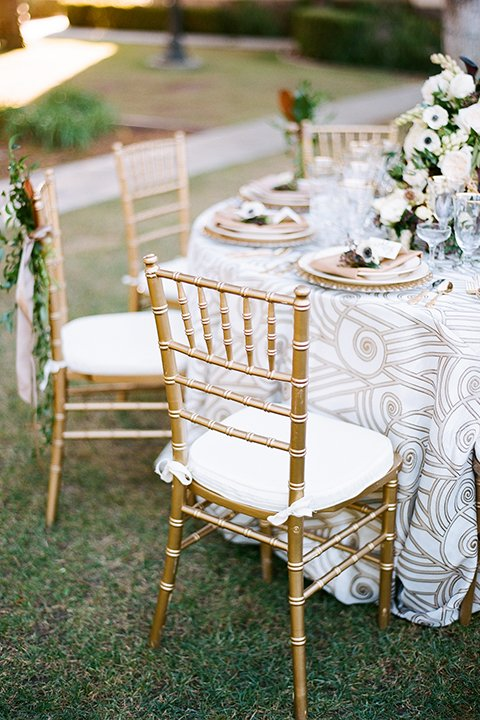 Glamorous outdoor wedding shoot at camarillo ranch house table set up with white lace linen and white and gold place settings with white and gold chairs with white flower centerpieces with gold napkin decor