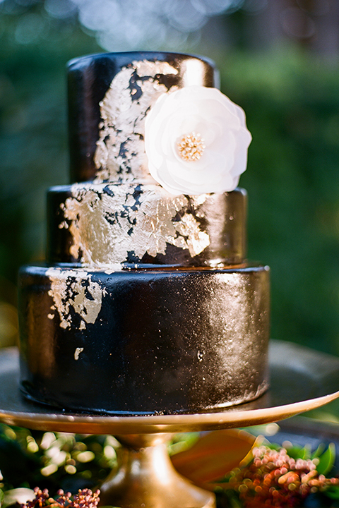 Glamorous outdoor wedding shoot at camarillo ranch house wedding cake three tier black wedding cake with gold design decor with white flower decor on side sitting on gold tray with green flower decor wedding photo idea for cake