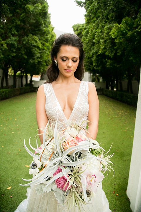Palm springs outdoor tropical wedding at the avalon hotel bride tulle a line gown with crystal beading design and thick straps with plunging neckline holding white and light pink floral bridal bouquet