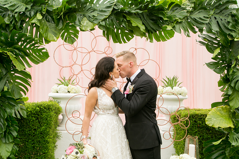 Palm springs outdoor tropical wedding at the avalon hotel bride tulle a line gown with crystal beading design and thick straps with plunging neckline with groom black tuxedo with matching vest and white dress shirt with black bow tie and pink floral boutonniere kissing by floral ceremony arch bride holding bouquet