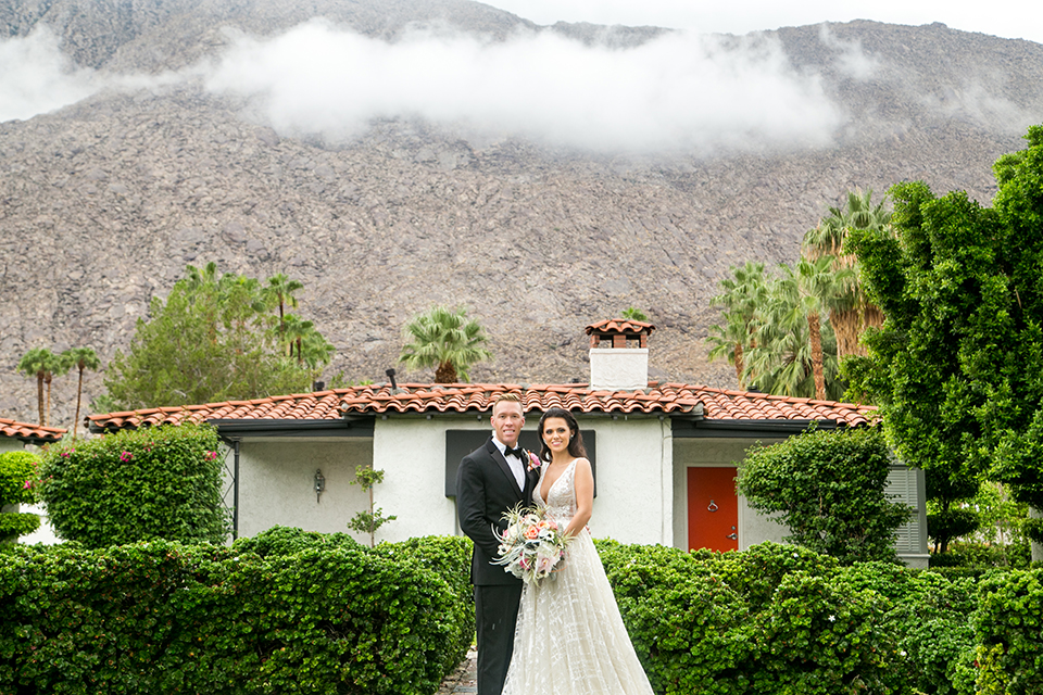 Palm springs outdoor tropical wedding at the avalon hotel bride tulle a line gown with crystal beading design and thick straps with plunging neckline with groom black tuxedo with matching vest and white dress shirt with black bow tie and pink floral boutonniere standing and bride holding white and pink floral bridal bouquet