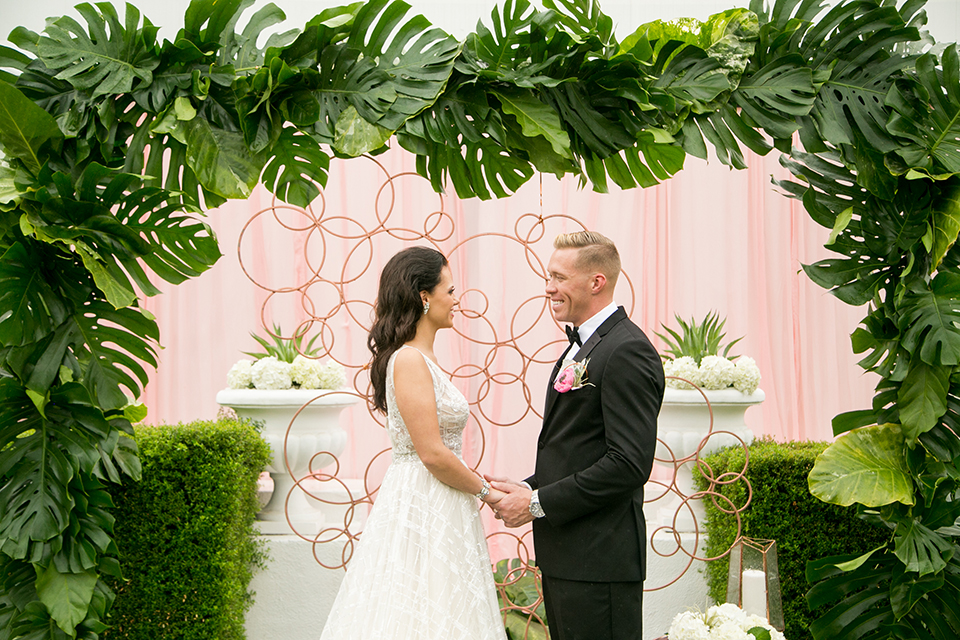 Palm springs outdoor tropical wedding at the avalon hotel bride tulle a line gown with crystal beading design and thick straps with plunging neckline with groom black tuxedo with matching vest and white dress shirt with black bow tie and pink floral boutonniere holding hands during ceremony by leaf floral arch