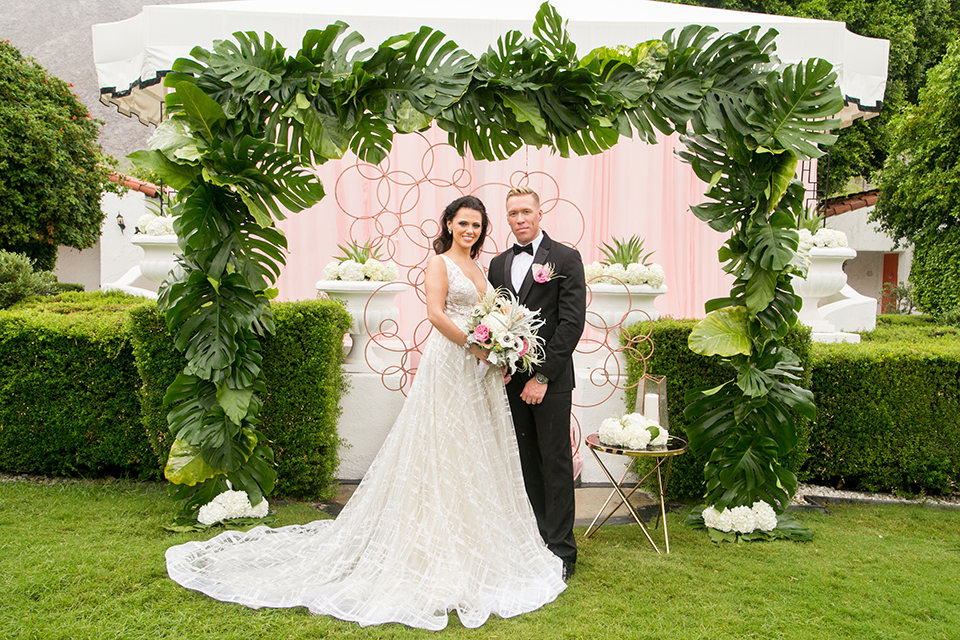 Palm springs outdoor tropical wedding at the avalon hotel bride tulle a line gown with crystal beading design and thick straps with plunging neckline with groom black tuxedo with matching vest and white dress shirt with black bow tie and pink floral boutonniere standing during ceremony under big green leaf floral arch bride holding white and pink floral bridal bouquet