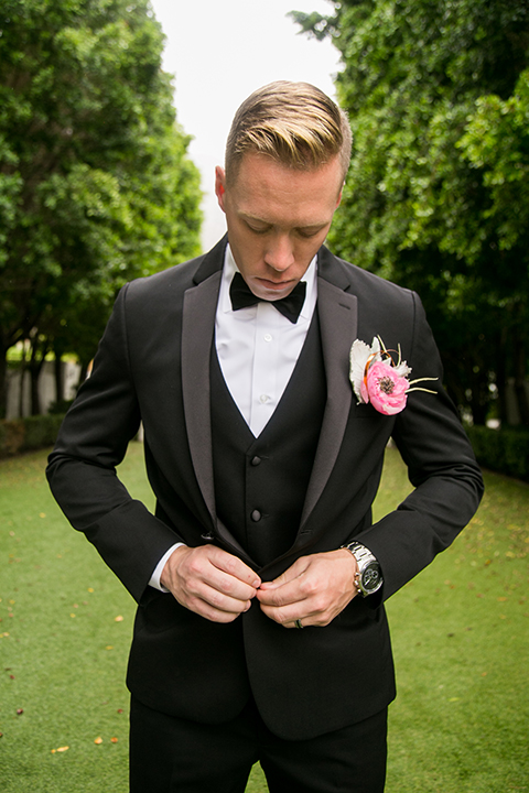 Palm springs outdoor tropical wedding at the avalon hotel groom black notch lapel tuxedo with matching vest and white dress shirt with black bow tie and pink floral boutonniere with silver watch buttoning jacket