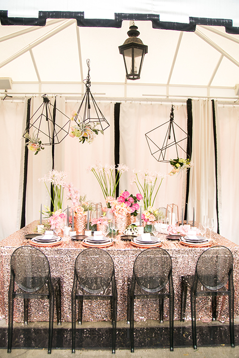 Palm springs outdoor tropical wedding at the avalon hotel gold sequined table linen with black chairs and gold plates with black and white place settings and pink flower centerpiece decor with gold silverware and black small plates with hanging flower decor
