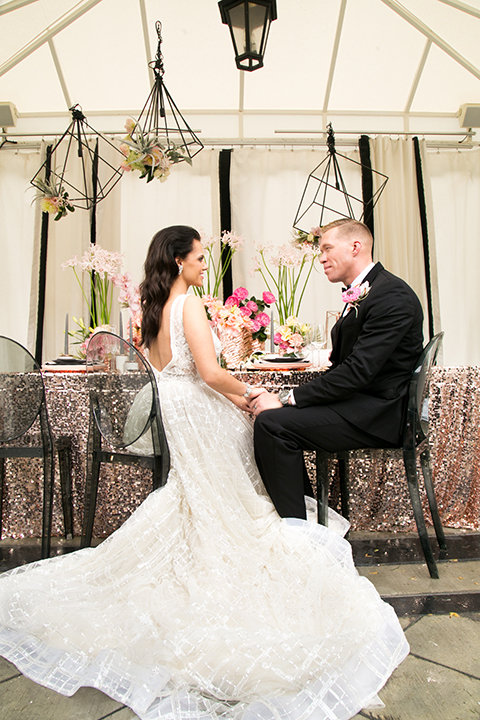 Palm springs outdoor tropical wedding at the avalon hotel bride tulle a line gown with crystal beading design and thick straps with plunging neckline with groom black tuxedo with matching vest and white dress shirt with black bow tie and pink floral boutonniere sitting at table