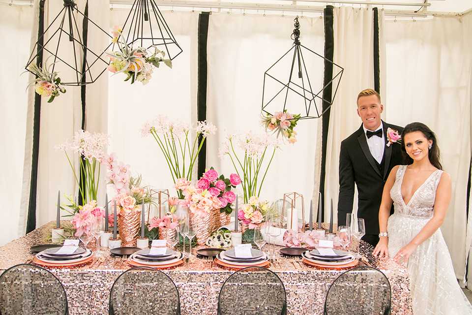 Palm springs outdoor tropical wedding at the avalon hotel bride tulle a line gown with crystal beading design and thick straps with plunging neckline with groom black tuxedo with matching vest and white dress shirt with black bow tie and pink floral boutonniere standing by table sequined table linen with black and white place settings and flower decor
