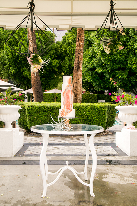 Palm springs outdoor tropical wedding at the avalon hotel four tier white wedding cake with orange geode rock formation on side on gold tray sitting on clear and white table wedding photo idea for cake