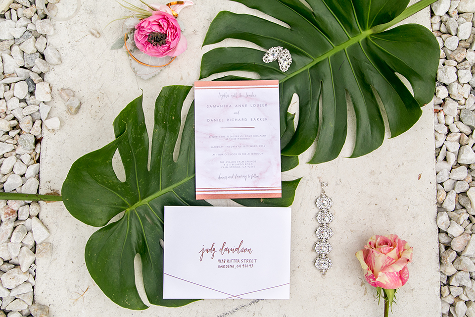 Palm springs outdoor tropical wedding at the avalon hotel white and light pink wedding invitations with pink flower decor on big green tropical leaves and white background wedding photo idea for wedding invitations
