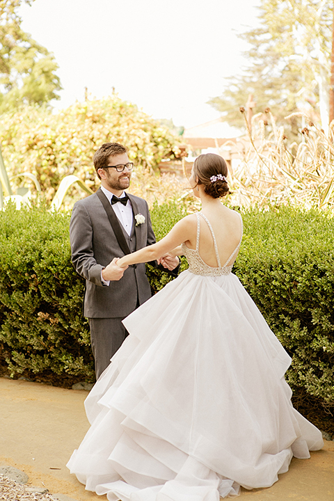 San juan capistrano outdoor wedding at serra plaza bride ruffled ballgown with beaded bodice and straps with open back design and long veil with crystal hairpiece with groom charcoal grey tuxedo with matching vest and white dress shirt with black bow tie and white floral boutonniere holding hands after first look