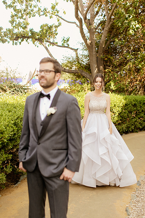 San juan capistrano outdoor wedding at serra plaza bride ruffled ballgown with beaded bodice and straps with open back design and long veil with crystal hairpiece with groom charcoal grey tuxedo with matching vest and white dress shirt with black bow tie and white floral boutonniere bride walking behind groom for first look