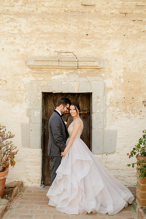 San juan capistrano outdoor wedding at serra plaza bride ruffled ballgown with beaded bodice and straps with open back design and long veil with crystal hairpiece with groom charcoal grey tuxedo with matching vest and white dress shirt with black bow tie and white floral boutonniere holding hands